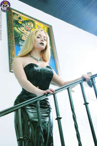 Spooky blond in black rubber dress on stairs