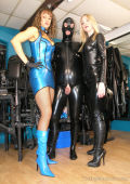 Rubber slave and two Dommes