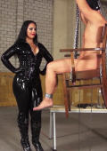 Latex Domina and slave on bondage chair